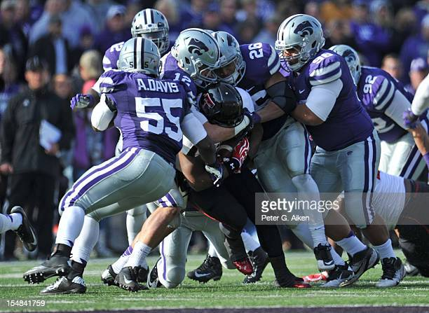 Defenders Adam Davis Ty Zimmerman Jarell Childs and Vai Lutui of the Kansas State Wildcats tackle running back Kenny Williams of the Texas Tech Red...