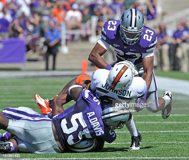 Defenders Jarard Milo and Adam Davis of the Kansas State Wildcats tackle running back Duke Johnson of the Miami Hurricanes during the second quarter...