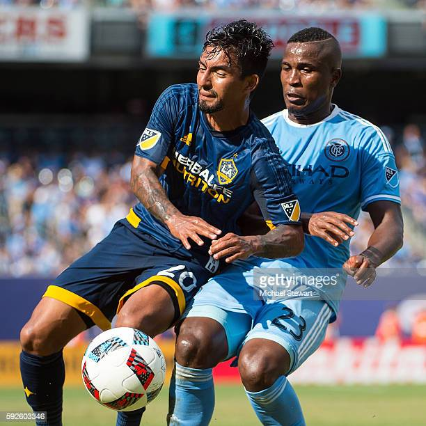 Defenders Jefferson Mena of New York City FC and A J DeLaGarza of Los Angeles Galaxy vie for the ball during the match at Yankee Stadium on August 20...