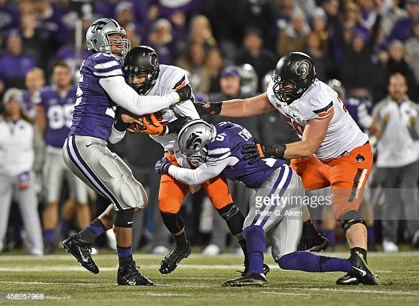 Defenders Jordan Willis and Randall Evans of the Kansas State Wildcats tackle quarterback Daxx Garman of the Oklahoma State Cowboys during the first...