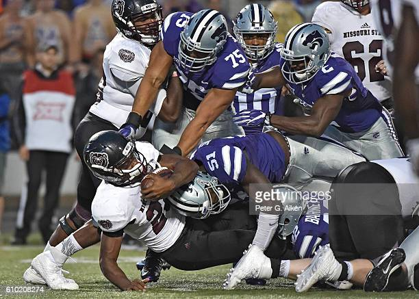 Defenders Jordan Willis and Reggie Walker of the Kansas State Wildcats tackle running back Calan Crowder of the Missouri State Bears for a loss,...
