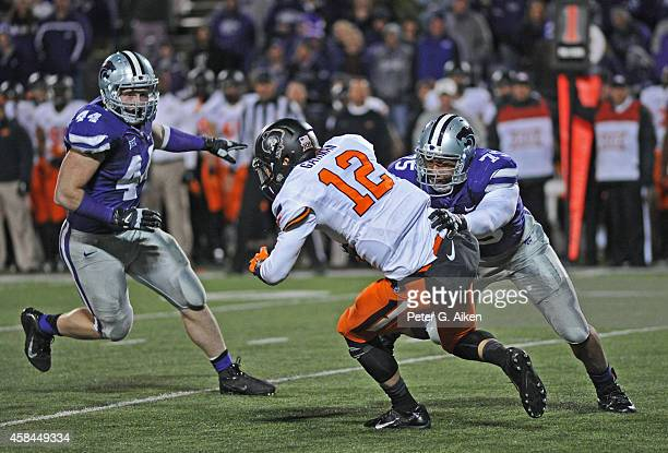 Defenders Jordan Willis and Ryan Mueller of the Kansas State Wildcats pressure quarterback Daxx Garman of the Oklahoma State Cowboys during the...