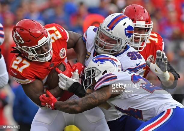 Defenders Leonard Johnson and Kyle Williams of the Buffalo Bills tackle running back Kareem Hunt of the Kansas City Chiefs during the first half at...
