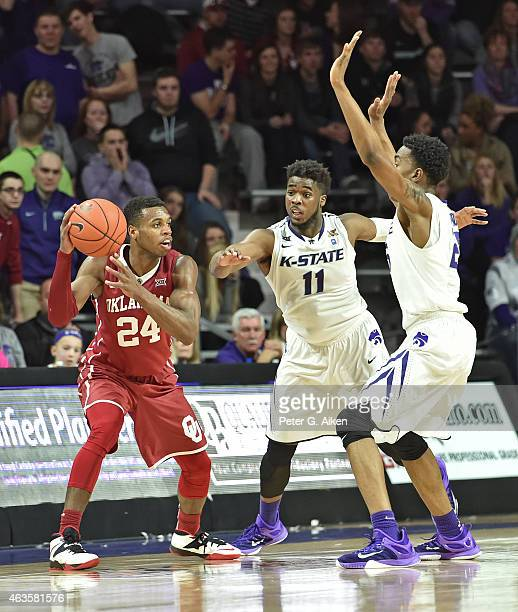 Defenders Nino Williams and Wesley Iwundu of the Kansas State Wildcats pressure guard Buddy Hield of the Oklahoma Sooners during the second half on...