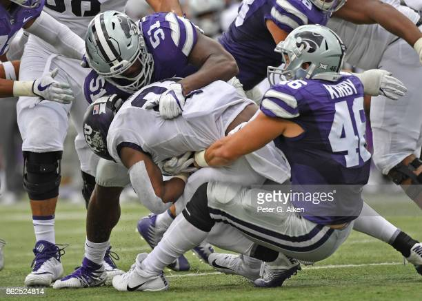 Defenders Reggie Walker and Jayd Kirby of the Kansas State Wildcats tackle running back running back Kyle Hicks of the TCU Horned Frogs during the...
