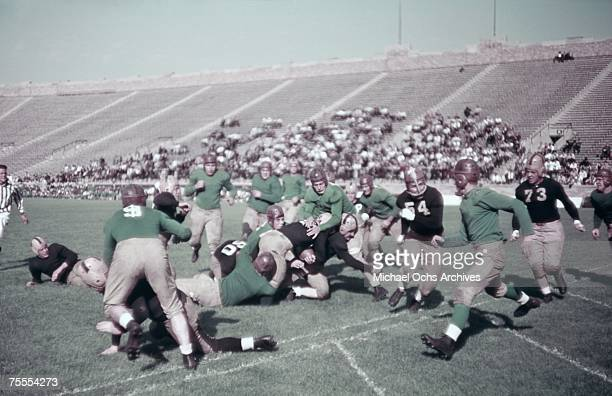 Defenders swarm the ballcarrier before he can reach the goal line during a high school football game circa 1939.