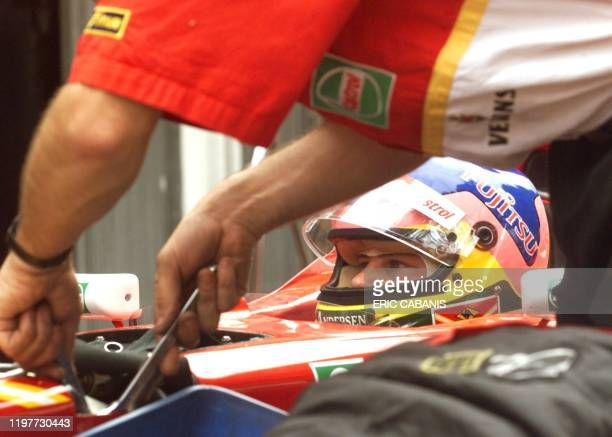 Defending Canadian world champion Jacques Villeneuve sits in his cockpit as a technician works on his car 23 May during the free practice sessions of...
