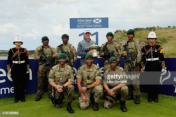Defending Champion Justin Rose of England holds the Scottish Open trophy alongside a troop of Royal Marines from the 43 Commando and Buglers Samanth...
