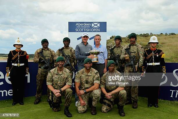 Defending Champion Justin Rose of England holds the Scottish Open trophy alongside Malcolm Duck local restaurateur a troop of Royal Marines from the...