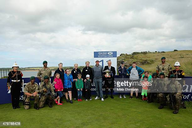 Defending Champion Justin Rose of England stands alongside Robert Dick Gullane Golf Club Captain Sophie Dow Founder of Mindroom children associated...
