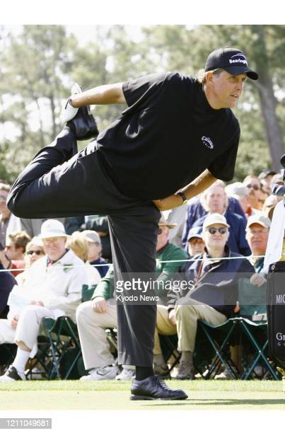 Defending champion Phil Mickelson stretches his quadriceps before teeing off on the opening hole during the first round of the Masters Tournament in...