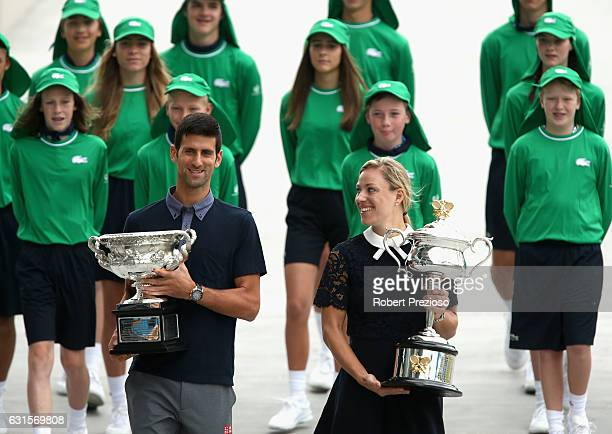 Defending champions Novak Djokovic of Serbia and Angelique Kerber of Germany carry the Australian Open trophies prior to the official draw ahead of...