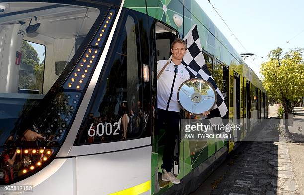 Defending Formula One Australian Grand Prix Nico Rosberg of Germany poses onboard an iconic Melbourne tram holding this year's trophy outside the...