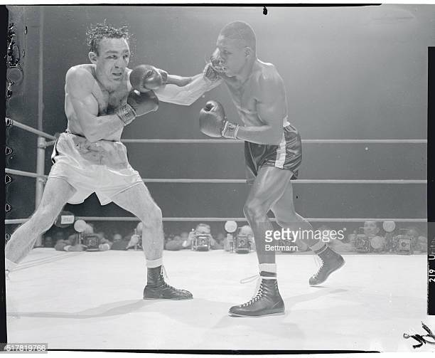 Defending welterweight champ Carmen Basilio ducks attack by challenger Johnny Saxton during the 12th round of the title bout here March 14 Saxton won...