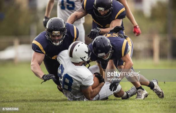 Defense American football players tackling opposite's team quarterback.