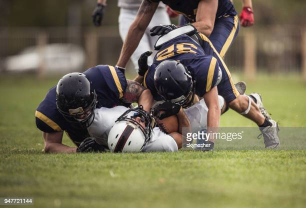 defense american football players tackling opposite's team quarterback. - tackling stock pictures, royalty-free photos & images