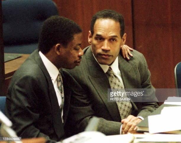 Defense attorney Carl Douglas puts his arm around defendant OJ Simpson during his double-murder trial 03 February in Los Angeles. Prosecutors...