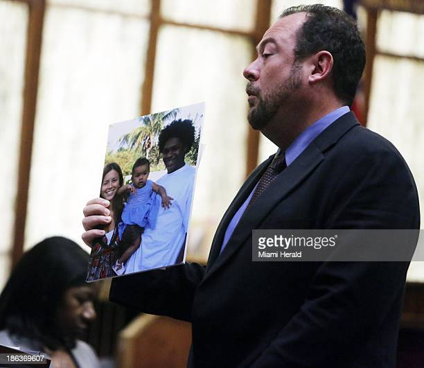 Defense attorney Chris Brown holds up a family photo of murdered football star Sean Taylor who is pictured with girlfriend Jackie Garcia Haley and...