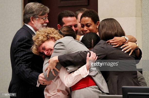 Defense attorney Dorothy Clay Sims, in gray jacket, hugs her client Casey Anthony, along with the rest of the defense team after Anthony was...