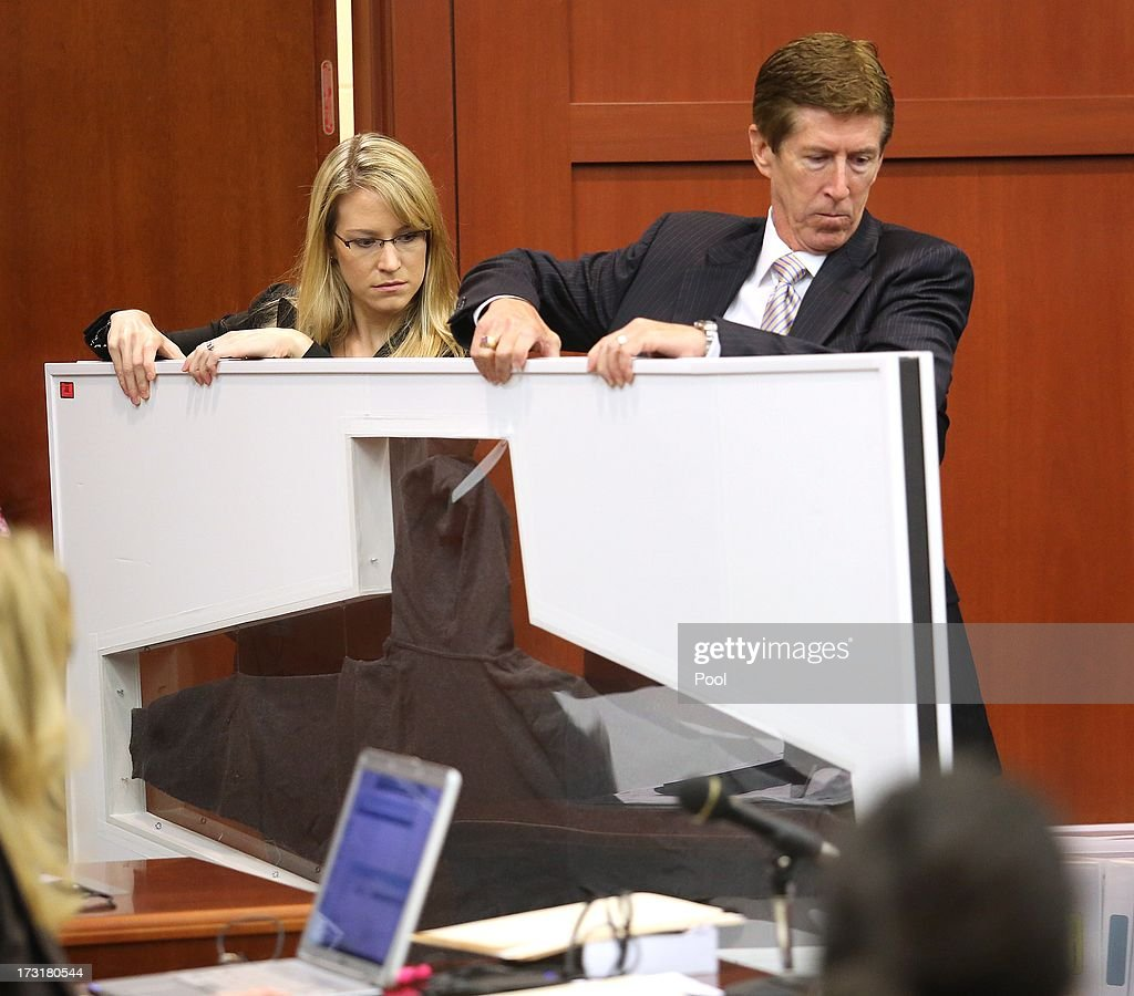 Defense counsel Mark O'Mara and an assistant carry in Trayvon Martin's hoodie in the George Zimmerman trial in Seminole circuit court, July 9, 2013 in Sanford, Florida. Zimmerman has been charged with second-degree murder for the 2012 shooting death of Trayvon Martin.