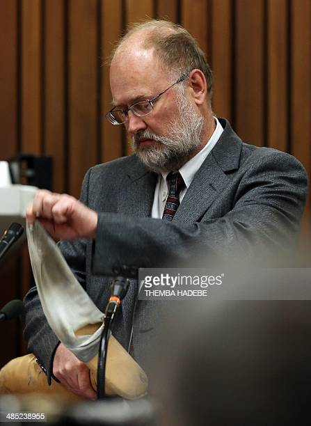 Defense expert witness Roger Dixon pulls off a sock from a prosthesis during the trial of South African Paralympian Oscar Pistorius on April 17 2014...