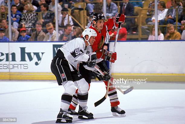 Defense Keith Brown of the Chicago Blackhawks fights for position with Center Wayne Gretzky of the Los Angeles Kings during a game at the Great...