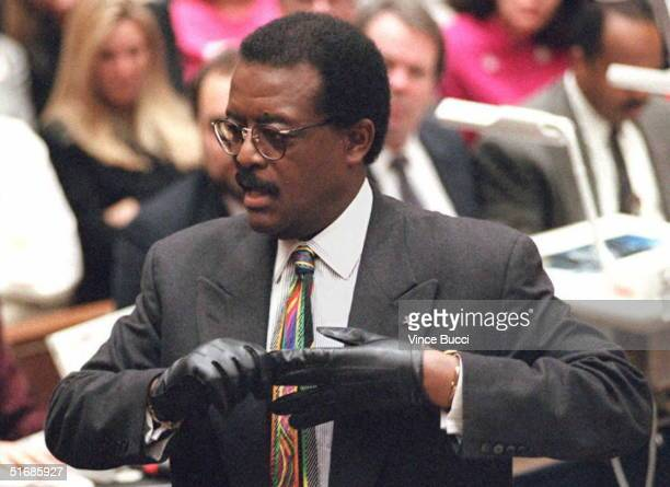 Defense lawyer Johnnie Cochran Jr puts on a gloves 27 September while he addresses the jury during closing arguments during the OJ Simpson double...