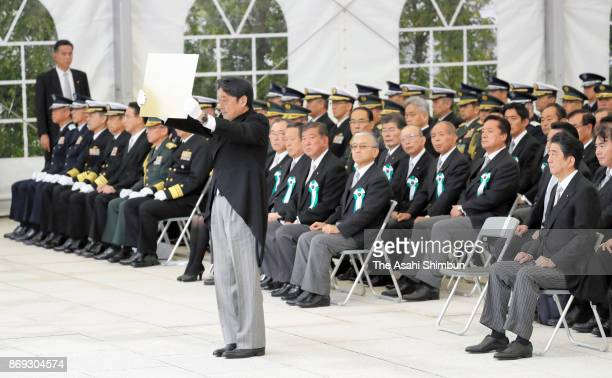 Defense Minister Itsunori Onodera dedicates the list of SelfDefense Force members who lost their lives on duty during the ceremony at the Defense...
