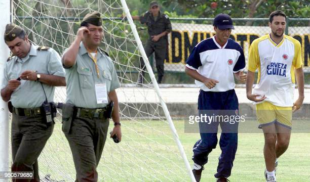 Defense player of the Colombian soccer team Mario Yepes jogs with assistent coach Alexis Garcia while guarded by Colombian National Police officers...