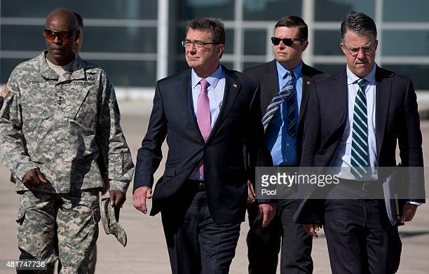 S Defense Secretary Ash Carter accompanied by his Chief of Staff Eric Rosenbach and US Army Lt Gen Ron Lewis walks on the tarmac before boarding his...