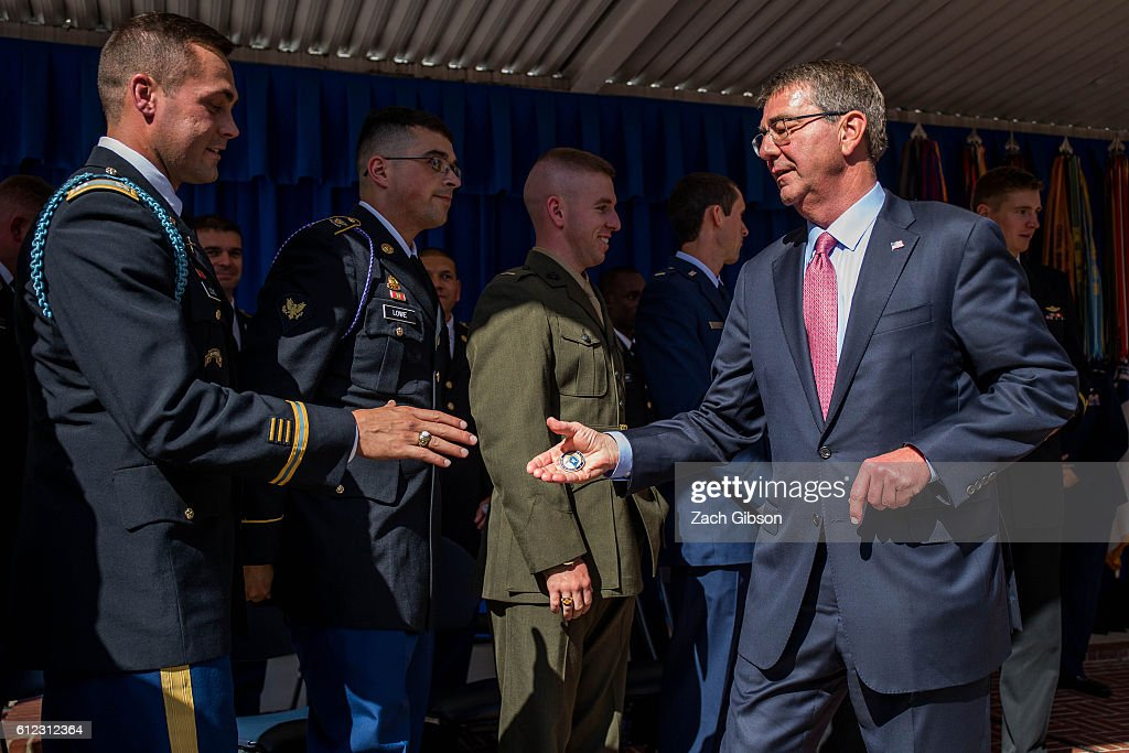 U.S. Defense Secretary Ash Carter hands out challenge coins during a ceremony honoring 2016 active duty military Olympians and Paralympians at The Pentagon on October 3, 2016 in Arlington, Virginia. The ceremony hosted 20 members of the U.S. military who competed in the 2016 games.