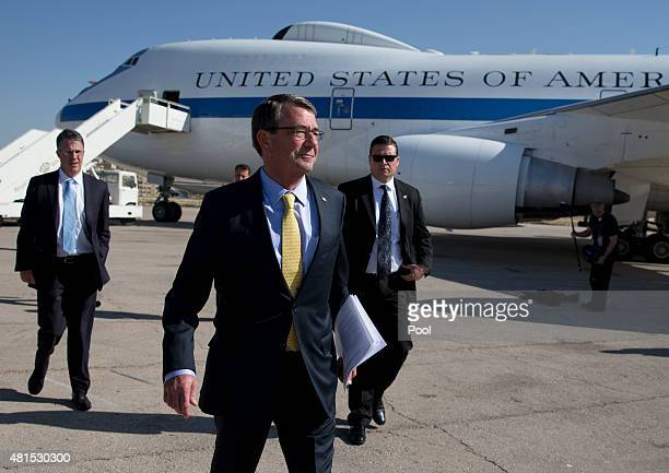 S Defense Secretary Ash Carter walks along the tarmac with Chief of Staff Eric Rosenbach left and a member of his security team before boarding a E4B...