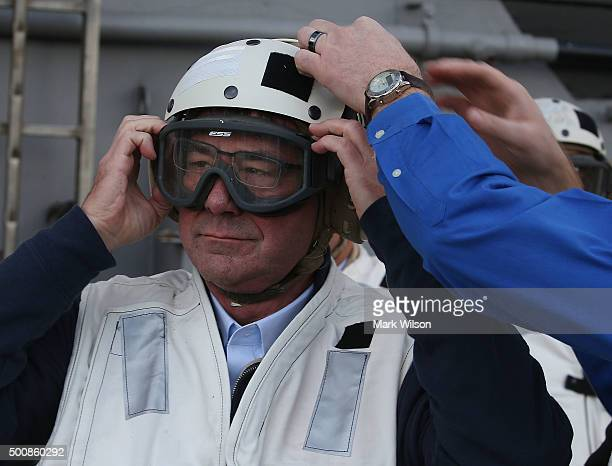 Defense Secretary Ashton Carter puts on a protective cranial helmet before watching F18 Super Hornets takes off from the flight deck of the USS...