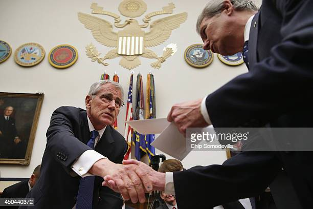 Defense Secretary Chuck Hagel greets members of the House Armed Services Committee during a break in testimony before the committee about the about...