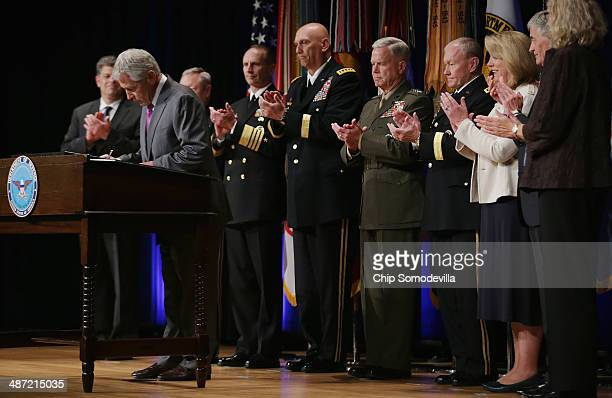 S Defense Secretary Chuck Hagel signs the Department of Defense Human Goals Charter with Director of Administration and Management Michael Rhodes...