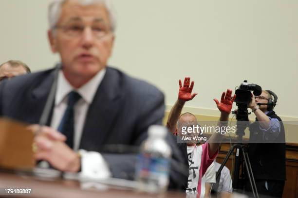 S Defense Secretary Chuck Hagel testifies as CodePink member Tighe Barry protests during a hearing on 'Syria Weighing the Obama Administration's...
