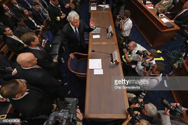 Defense Secretary Chuck Hagel waves to members of Congress before testifying to the House Armed Services Committee about the about the prisoner...