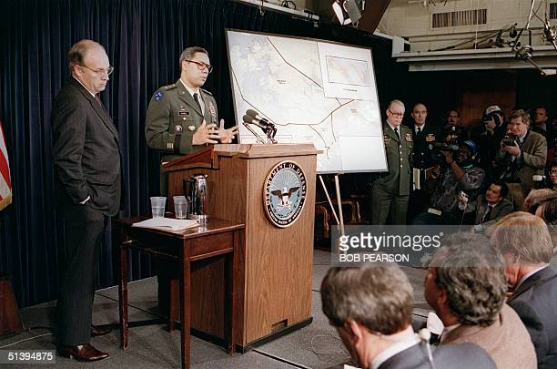 Defense Secretary Dick Cheney stands by as General Colin Powell chairman of the Joint Chiefs of Staff briefs reporters at the Pentagon 20 December...
