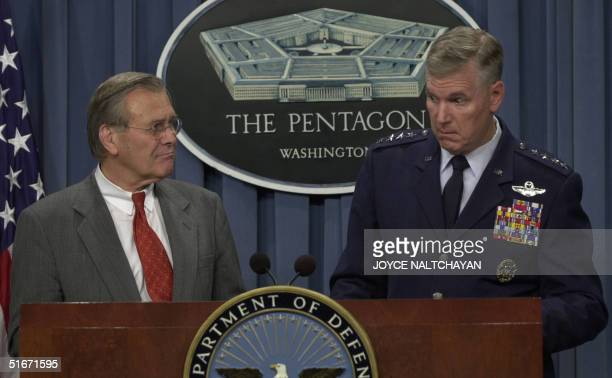 Defense Secretary Donald Rumsfeld looks on as US Air Force General Richards Myers, Chairman of the Joint Chiefs of Staff, answers reporters questions...