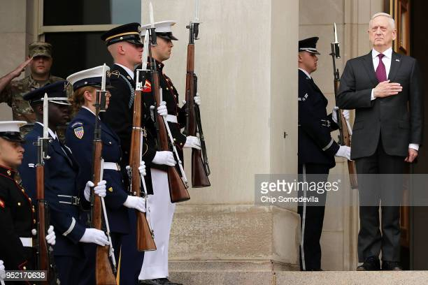 S Defense Secretary James Mattis puts his hand over his heart during the playing of the national anthem as he hosts an Enhanced Honor Cordon for...