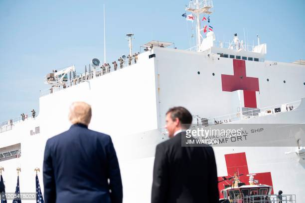 US Defense Secretary Mark Esper and US President Donald Trump watch as the hospital ship USNS Comfort departs Naval Base Norfolk on March 28 in...