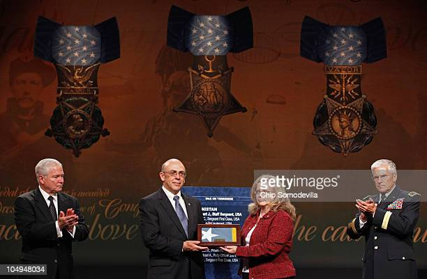 S Defense Secretary Robert Gates and Army Chief of Staff Gen George Casey Jr applaud after presenting US Army Staff Sgt Robert Miller's parents...