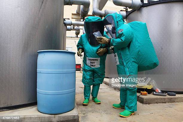 CBRN defense specialists check a barrel for contamination.