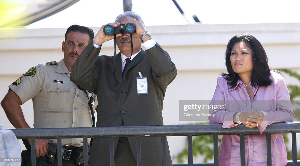 Defense team member Scott Ross (C) and defense witness Monica De Los Santos (R) look out over the Santa Barbara County Courthouse grounds while Michael Jackson's child molestation trial is in proceedings May 23, 2005 in Santa Maria, California. Jackson is charged in a 10-count indictment that included molesting a boy, plying him with liquor and conspiring to commit child abduction, false imprisonment and extortion. He has pleaded innocent.