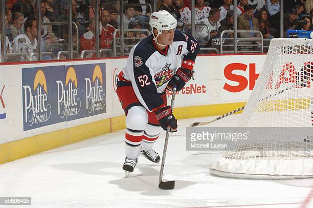 Defenseman Adam Foote of the Columbus Blue Jackets plays the puck behind the net against the Washington Capitals during the NHL game on October 5...