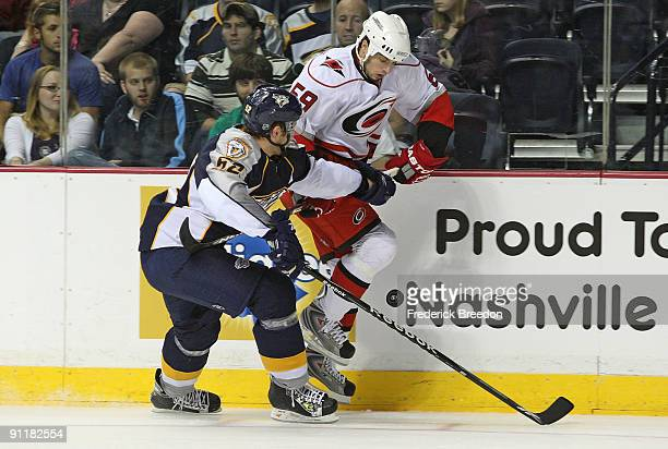 Defenseman Alexander Sulzer of the Nashville Predators fights for the puck against forward Chad LaRose of the Carolina Hurricanes during a preseason...