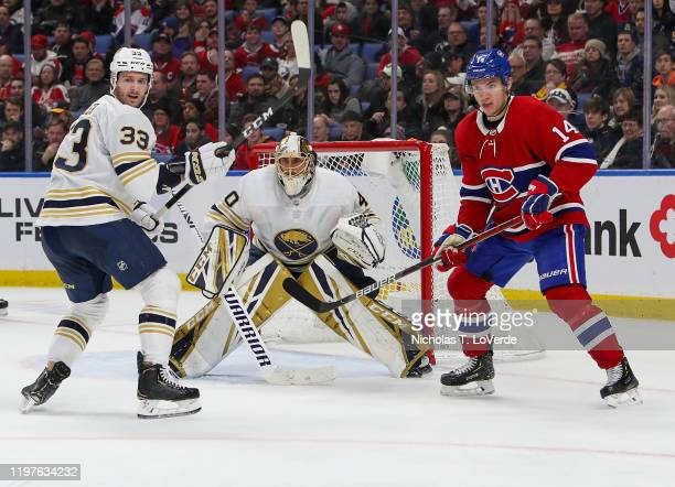 Defenseman Colin Miller and Carter Hutton of the Buffalo Sabres defend the Buffalo net against Nick Suzuki of the Montreal Canadiens during the third...