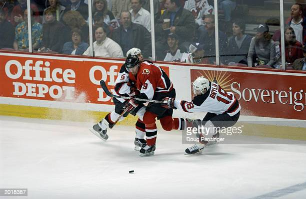 Defenseman Colin White and forward Sergei Brylin of the New Jersey Devils check Martin Havlat of the Ottawa Senators in game three of the Eastern...