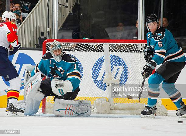 Defenseman Colin White and goaltender Thomas Greiss of the San Jose Sharks defend the goal against left wing Tomas Fleischmann of the Florida...