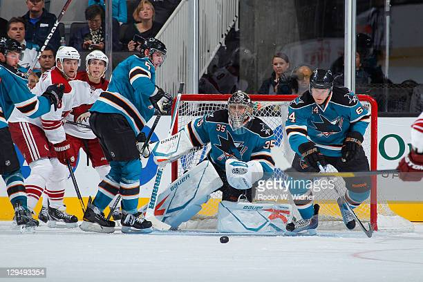 Defenseman Colin White goaltender Harri Sateri and left wing Jamie McGinn of the San Jose Sharks look to defend the goal against the Phoenix Coyotes...